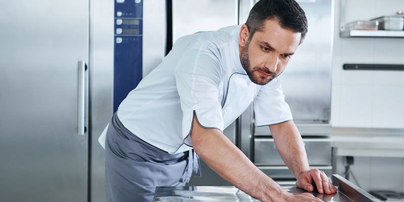 Chef cleaning his restaurants kitchen equipment as part of his maintenance routine