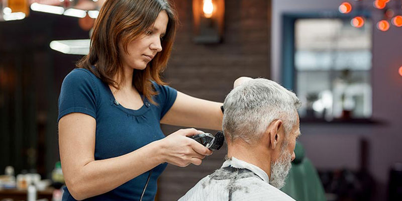 Hair stylist cutting hair of a customer with a buzzer in a barbershop