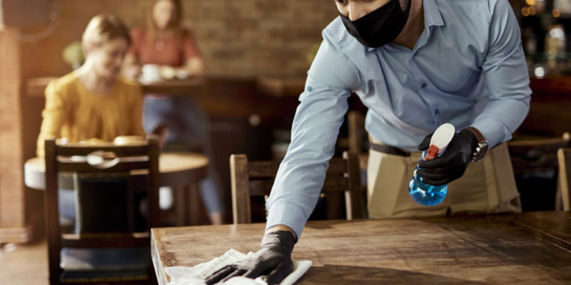 Food and beverage employee cleaning a table at a restaurant