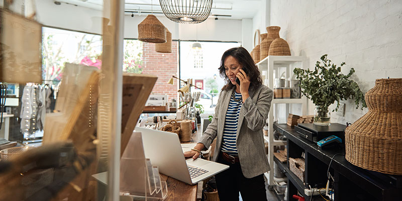 Business owner of retail shop on phone with customer