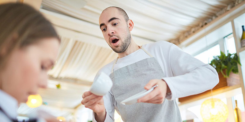 employee spilling coffee on dinning guest